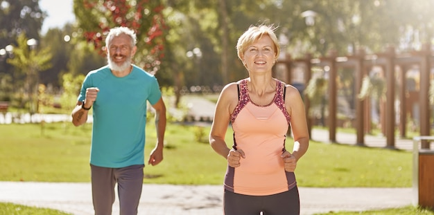 Pour une meilleure santé, un couple familial mature et actif en vêtements de sport a l'air heureux tout en courant ensemble dans