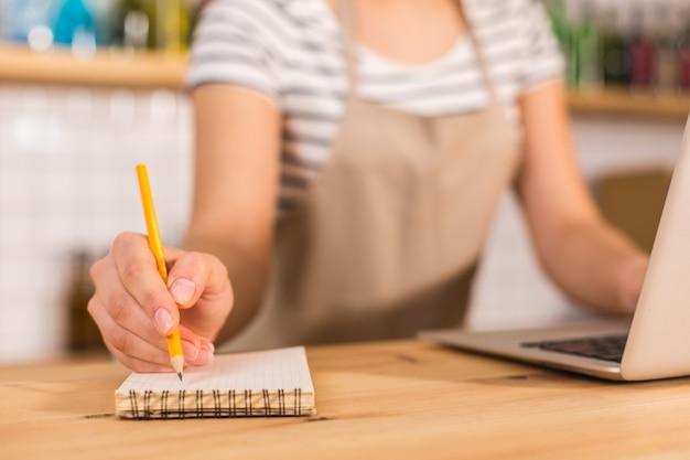 Pour les notes. mise au point sélective d'un ordinateur portable utilisé par une belle femme agréable intelligente tout en travaillant dans le café