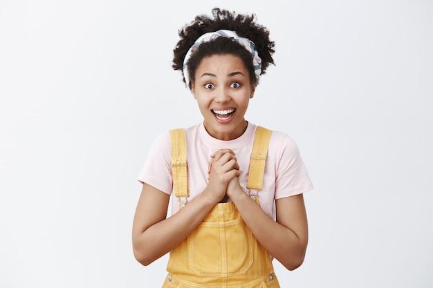 Pour De Vrai, Est-ce Pour Moi. Portrait De Touché Surpris Et Heureux Heureux Femme Afro-américaine En Salopette élégante Jaune Applaudissant Des Paumes Sur La Poitrine Et Souriant Largement Avec Un Regard Reconnaissant Photo gratuit