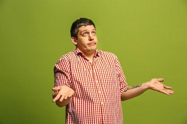 Pourquoi donc. beau portrait de demi-longueur masculin isolé sur fond de studio vert branché. jeune homme émotionnel surpris, frustré et déconcerté.