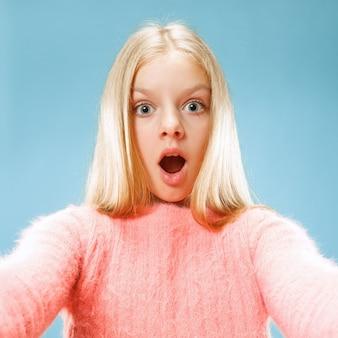 Pourquoi donc. beau portrait de femme demi-longueur sur fond de studio bleu à la mode. jeune adolescente émotive surprise, frustrée et déconcertée. émotions humaines, concept d'expression faciale.