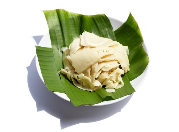 Pousse de bambou conservée sur feuille de bananier en plaque blanche