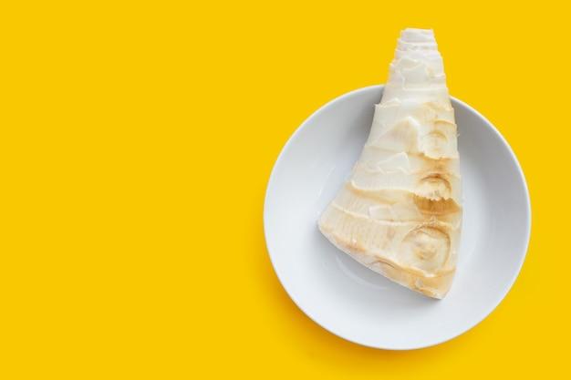 Pousse de bambou dans un bol blanc sur fond jaune