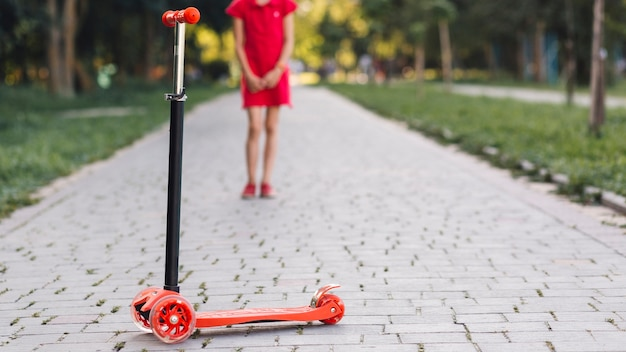 Pousser, scooter, devant, fille, debout, passerelle, dans parc