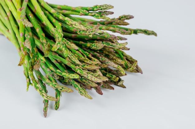 Pousses d'asperges vertes biologiques fraîches sur blanc. la nourriture saine.