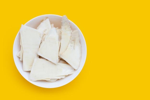 Pousses de bambou brutes tranchées dans un bol blanc sur fond jaune.
