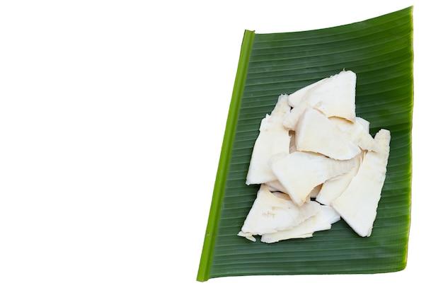 Pousses de bambou brutes tranchées sur feuille de bananier sur fond blanc.