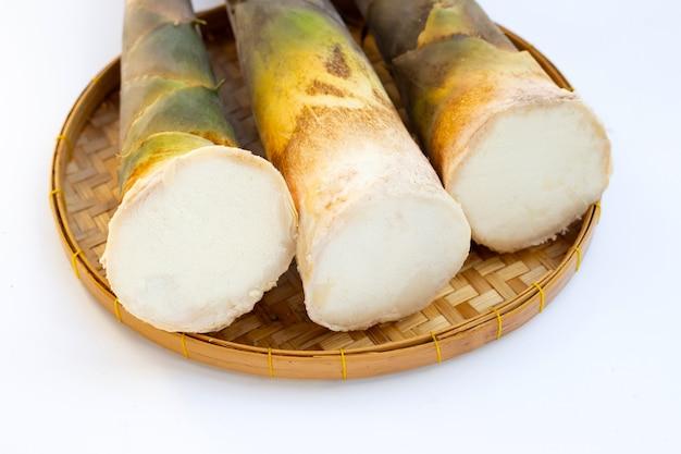 Pousses de bambou fraîches dans le panier sur fond blanc.