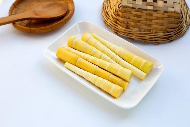 Pousses de bambou en plaque blanche sur fond blanc.