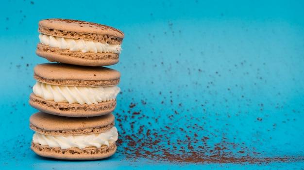 Poussière de chocolat avec des macarons sur fond bleu