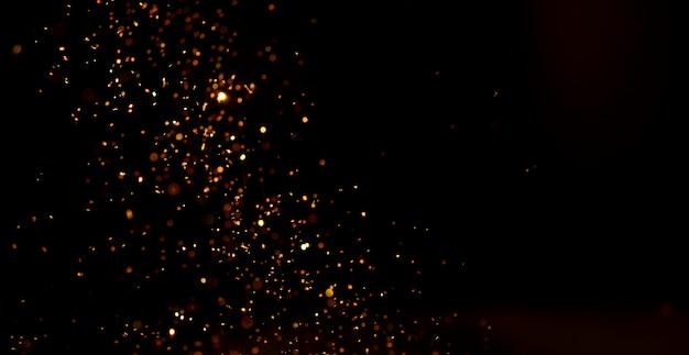 Poussière dorée abstraite sur la surface noire