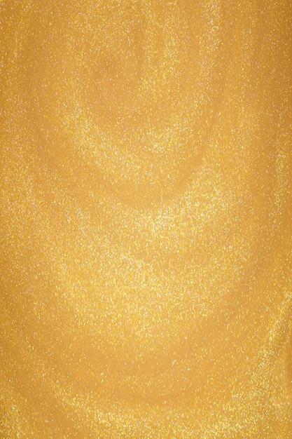 Poussière de paillettes dorées sur fond sombre.