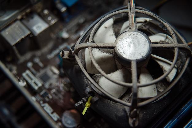 Poussière sur un refroidisseur de processeur d'ordinateur avec carte mère et fragment de boîtier d'ordinateur