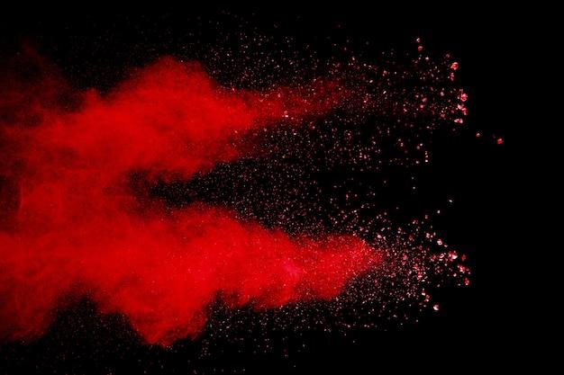 Poussière rouge abstraite éclaboussée sur fond noir. explosion de poudre rouge.