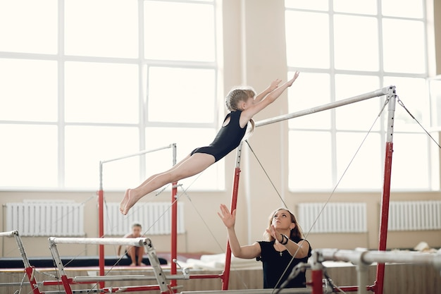 Poutre de gymnastique enfant. athlète gymnaste fille lors d'un exercice barre horizontale dans les compétitions de gymnastique. coach avec enfant.
