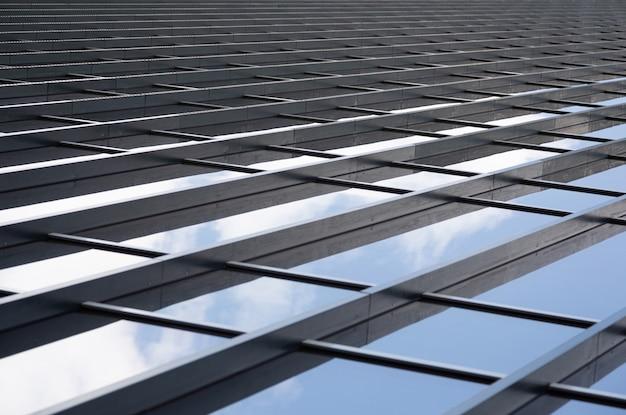 Poutres métalliques reliant les panneaux de verre d'un mur