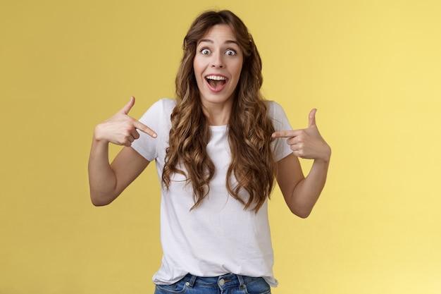 Pouvez-vous croire, fascinant. impressionné sociable jolie fille disant ami excellent près d'être choisi a obtenu un emploi pointant l'index elle-même centre copie espace t-shirt blanc regard surpris en souriant.