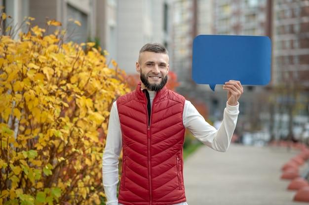 Le pouvoir des mots. beau jeune homme vous regarde tout en tenant une pancarte bleue