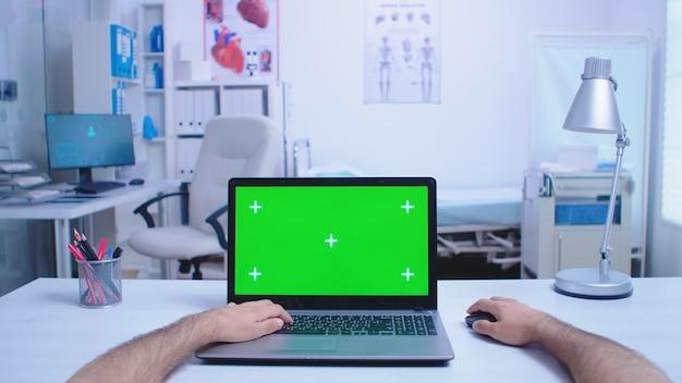 Pov d'un assistant utilisant un ordinateur portable avec un espace de copie disponible dans l'armoire de l'hôpital et un médecin travaillant sur ordinateur. médecin à l'aide d'un ordinateur portable avec une clé chroma exposée dans une clinique médicale.