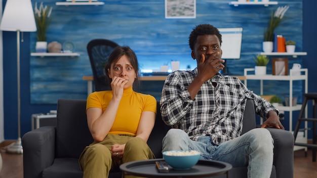Pov d'un couple interracial choqué regardant un film effrayant