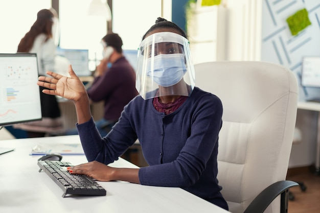 Pov d'un entrepreneur africain saluant lors d'un appel vidéo avec des hommes d'affaires portant un masque facial contre covid19. femme parlant avec l'équipe lors d'une conférence en ligne pendant que des collègues travaillent en arrière-plan.