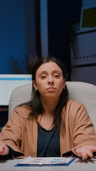 Pov d'une femme entrepreneur fatiguée assise à une table de bureau ayant un webinaire d'affaires discutant de la finance...