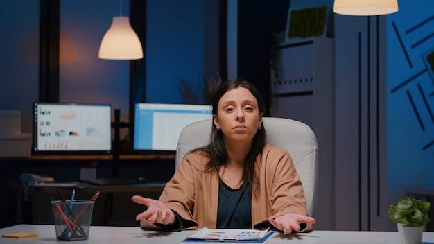 Pov d'une femme entrepreneur fatiguée assise à une table de bureau ayant un webinaire d'affaires