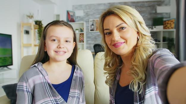 Pov d'une fille heureuse avec un appareil dentaire et sa mère faisant des grimaces devant la caméra.