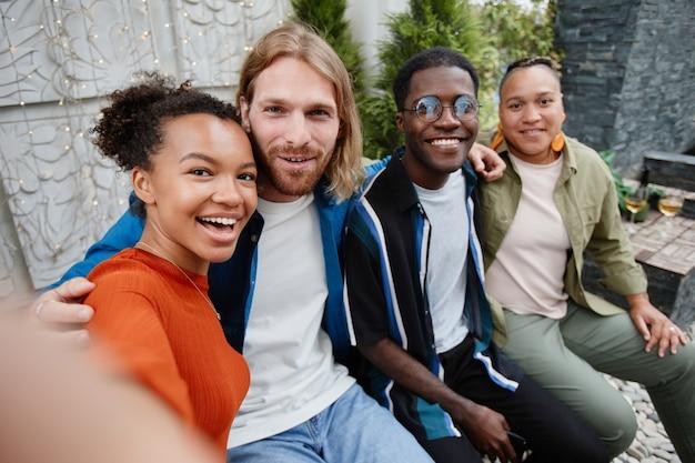 Pov groupe diversifié de jeunes regardant la caméra via un chat vidéo tout en s'amusant lors d'une fête en plein air sur le toit