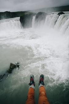 Pov sur les jambes des hommes en bottes sur la cascade de la falaise