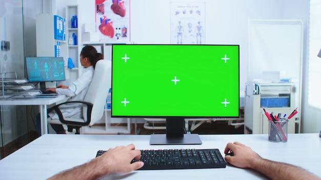 Pov de la main du médecin travaillant sur ordinateur avec écran vert dans le cabinet de l'hôpital. médecin dans le bureau de travail du cabinet de la clinique avec espace de copie disponible.