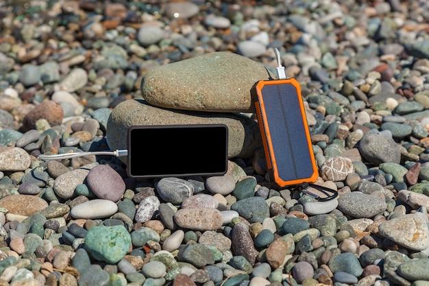 Le poverbank se trouve sur les galets au bord de la mer et charge le téléphone. powerbank charge le téléphone.