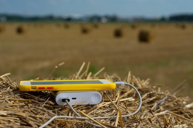 Power bank charge un smartphone à l'extérieur dans un champ dans le foin.