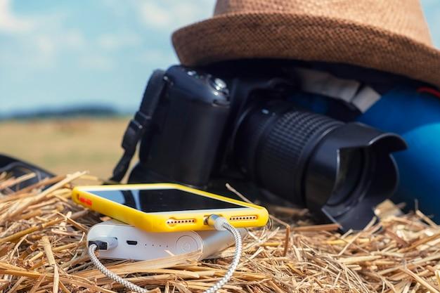 Power bank charge un smartphone sur fond d'appareil photo avec un sac et un chapeau sur fond de foin dans la nature. chargeur de voyage portable.