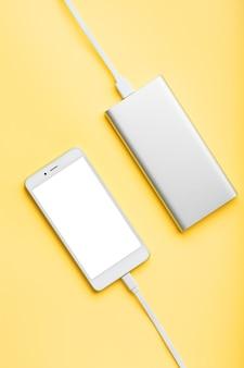 Power bank charge votre smartphone sur une surface rose