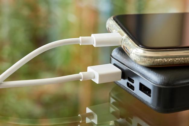 Powerbank charge le smartphone à l'aide d'un câble usb sur une surface en verre