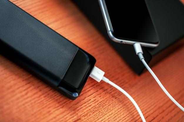Powerbank charge un smartphone isolé sur bois