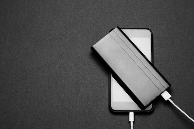 Powerbank charge smartphone isolé sur fond noir