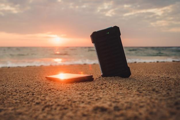 Powerbank dans le sable sur fond de soleil levant dans le ciel nuageux et la mer bleue. source d'énergie alternative. la batterie est chargée par l'énergie solaire. charger des appareils mobiles dans la nature. île.