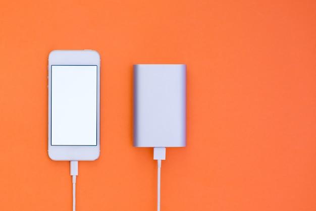 Powerbank et téléphone sur fond orange. mise en page du téléphone à plat qui charge avec powerbank