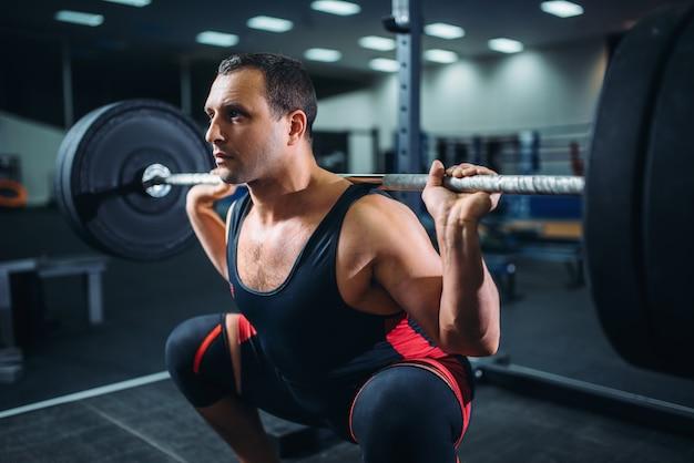 Powerlifter faisant des squats avec haltères dans une salle de sport