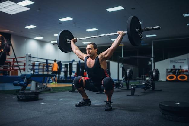 Powerlifter fort faisant deadlift une barre dans une salle de sport