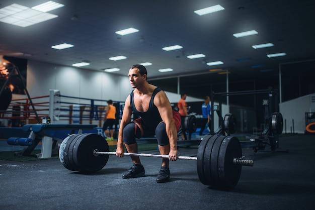 Powerlifter mâle commençant deadlift une barre dans la salle de gym.