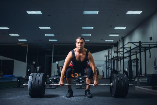 Powerlifter mâle démarrage haltères deadlift dans une salle de sport