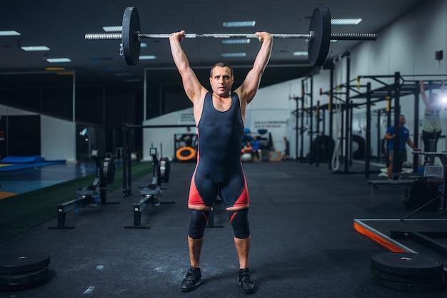 Powerlifter mâle fort faisant deadlift une barre dans la salle de gym.