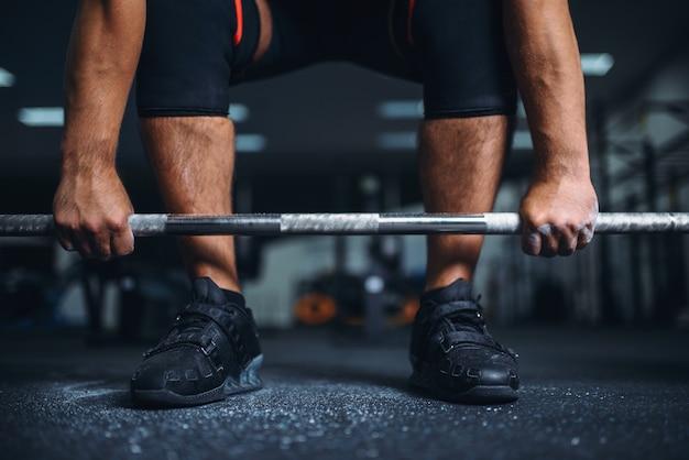 Powerlifter se prépare pour deadlift une barre dans une salle de sport