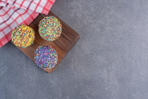 Pralines colorées décorées de paillettes sur planche de bois.