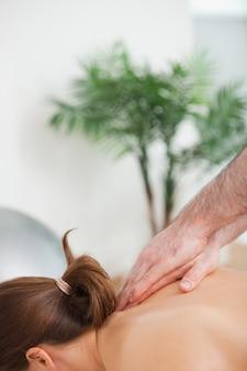 Praticien massant le haut du dos de son patient à l'intérieur
