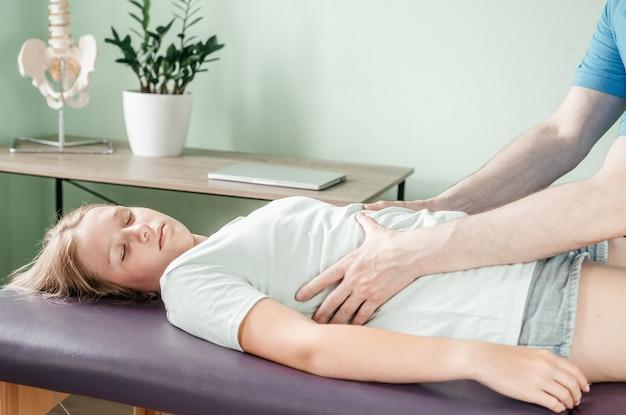 Praticien ostéopathe libérant le diaphragme d'une patiente, massage de libération de la cage thoracique, relaxation des muscles respiratoires