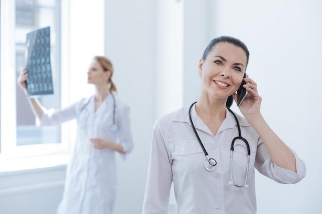 Praticienne mature souriante impliquée travaillant à la clinique et appréciant la conversation au téléphone pendant que son collègue tient une photo aux rayons x du cerveau et l'observe